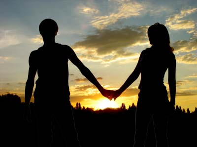 Loving couple holdind on the hands and sunset